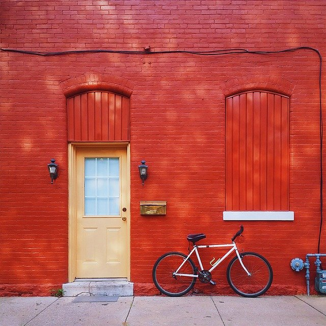 červená zeď, kolo, světlé dveře